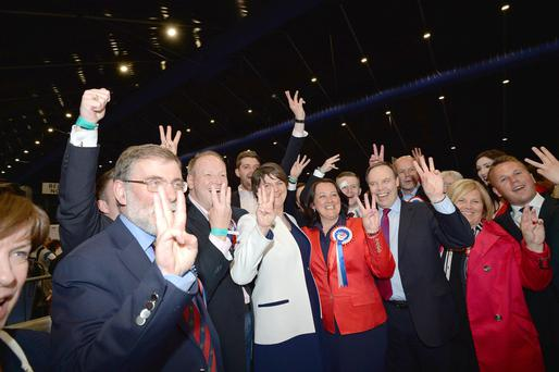 DUP leader and First Minister Arlene Foster celebrates with party colleagues at the Titanic Exhibition Centre in Belfast after taking three seats in North Belfast