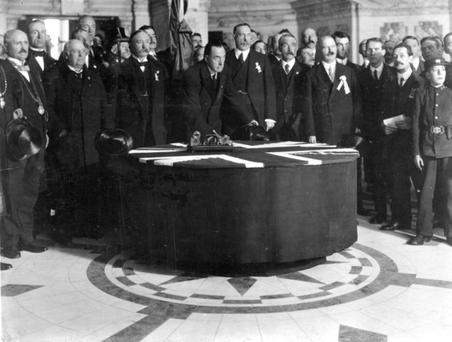Sir Edward Carson puts the first signature on the Ulster Covenant at Belfast City Hall in 1912. To the right of the photo is a telegram boy, believed to be Dennis Hanna