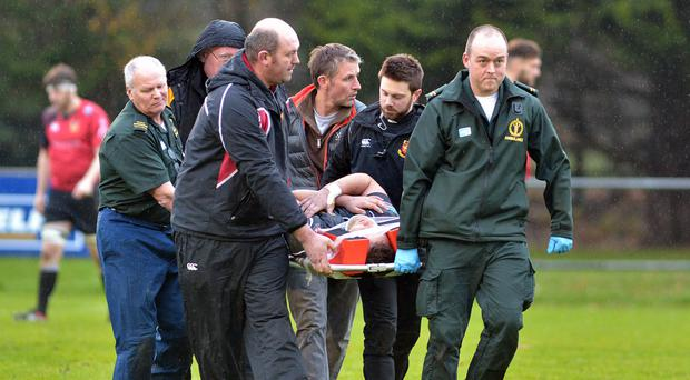 Ballymena's Mark Best is stretchered off the pitch during the match against Buccaneers