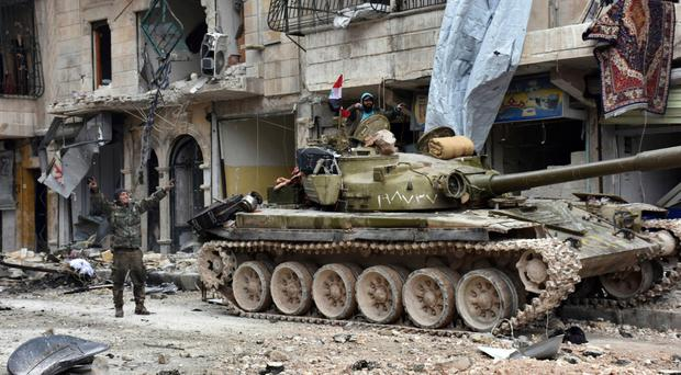 Syrian soldiers flash the victory sign after capturing all of Aleppo last week