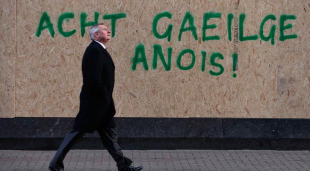 A man walks past graffiti calling for an Irish Language Act
