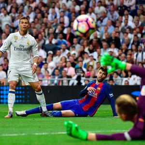 Real Madrid's Cristiano Ronaldo (left) gets a shot away under pressure from Barcelona defender Gerard Pique during the El Clasico battle at the Santiago Bernabeu stadium in Madrid on Sunday