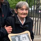 Teresa Watt, wife of Barney Watt, outside Belfast Coroner's Court with a photo of the couple on their wedding day