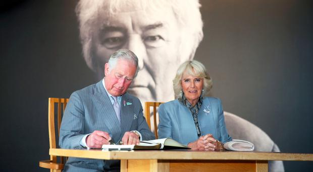 The Prince of Wales signs the visitors' book while the Duchess of Cornwall looks on during a tour of HomePlace last week