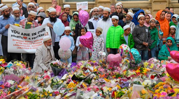 Members of the Muslim community gather yesterday at the floral tributes at St Ann's Square in Manchester