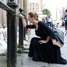A woman prays as she views floral tributes for the bomb victims left at St Ann's Church in Manchester
