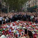 Spain's King Felipe (centre) stands with Queen Letizia and Catalonia regional president Carles Puigdemont (centre left) at a memorial to the victims at Las Ramblas in Barcelona