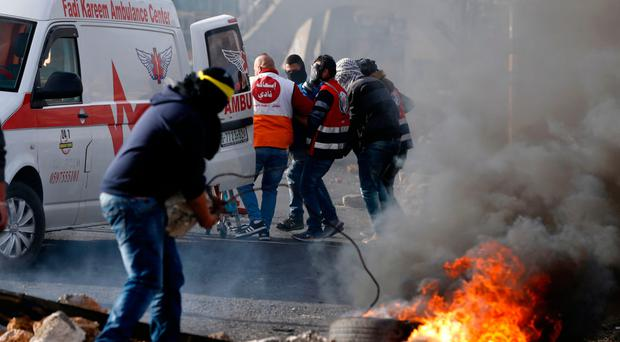 Palestinian paramedic volunteers carry away an injured protester during clashes with Israeli forces in the West Bank city of Ramallah