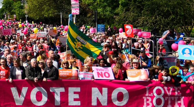 People hold up placards and banners during a Stand up for Life rally in Dublin calling for a 'No' vote in the upcoming referendum