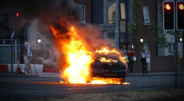 A car burns in east Belfast on the Upper Newtownards Road on the Eleventh night. Left: A petrol bomb explodes as a PSNI vehicle drives past in Londonderry on Monday night