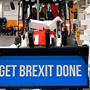 "Prime Minister Boris Johnson drives a Union flag-themed JCB, with the words ""Get Brexit Done"" inside the digger bucket, through a fake wall emblazoned with the word 'gridlock', during a general election campaign event"