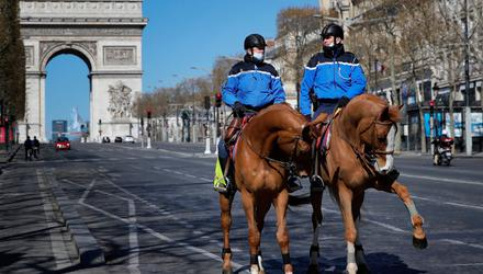 Mounted police patrol the empty Champs Elysees avenue in Paris