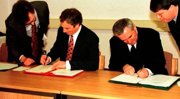 Tony Blair (left) and Bertie Ahern sign the peace agreement on Good Friday, April 1998
