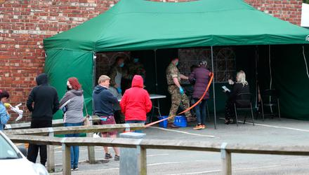 People queue at a walk-in coronavirus testing centre staffed by soldiers in Cheshire