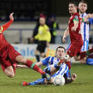 Sliding in: Cliftonville ace Joe Gormley is tackled by Coleraine's Adam Mullan
