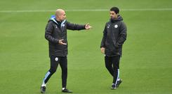 Winning team: Pep Guardiola and Mikel Arteta prepare for this evening's Manchester derby
