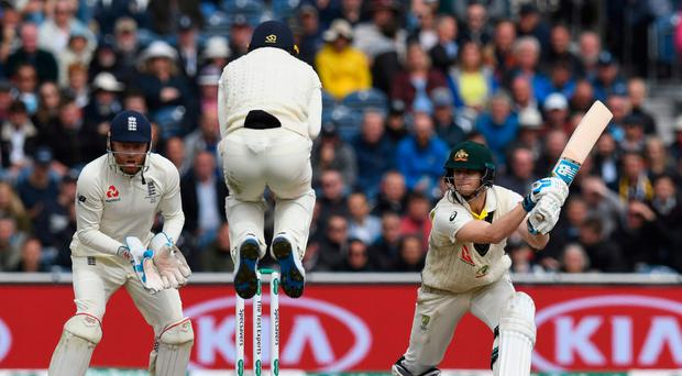 High jump: England's Jos Buttler jumps over the ball as Australia's Steve Smith goes on the attack during his double century