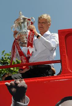 Arsene Wenger celebrates with the FA Cup onboard the Arsenal team bus