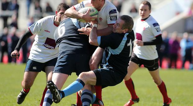 Double team: Malone's Jonathan Siri is tackled by Ballymoney's Aaron Ramage and Jarvis Traynor