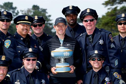 Laying down the law: Rory McIlroy with his Match Play title and members of the San Francisco police