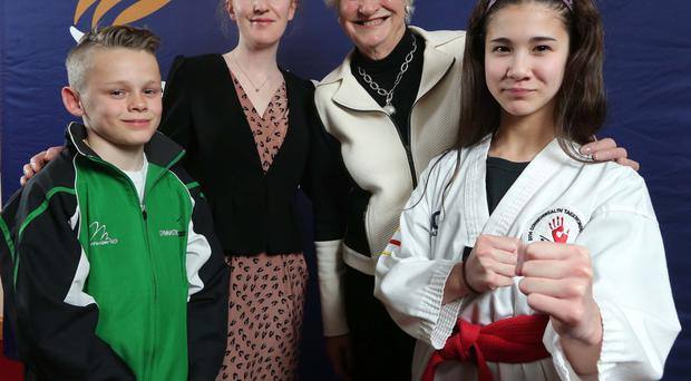 Helping hand: Collecting their awards from Dame Mary Peters and Laura Duggan of Belfast City Airport are gymnast Ronan McCrory and Taekwondo's Enya Robinson