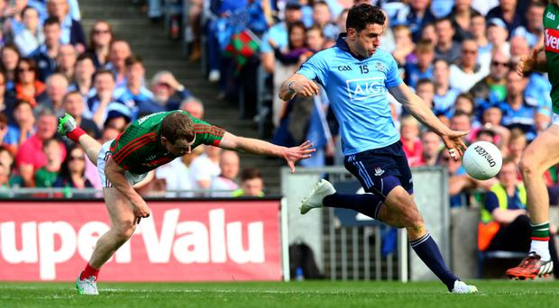 On point: Bernard Brogan of Dublin scores a point despite the efforts of Colm Boyle of Mayo