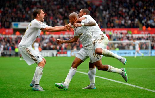 Striker Andre Ayew (centre) celebrates with Ashley Williams (right) and Gylfi Sigurdsson (left) after scoring his side's first goal