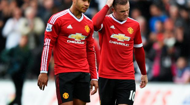 Lost moment: Memphis Depay and Wayne Rooney walk off the pitch in dejected mood after yesterday's defeat