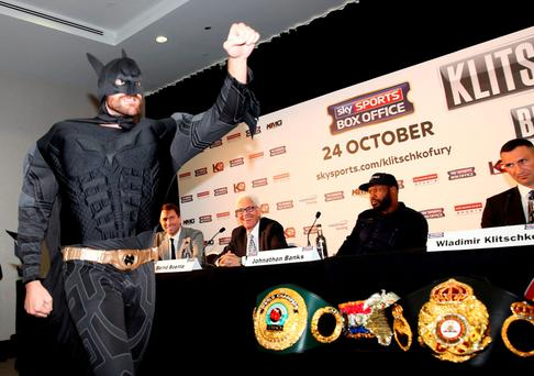 One-man crusade: Wladimir Klitschko looks unamused as Tyson Fury turns up to their press conference dressed as Batman