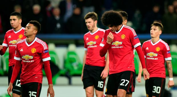 Trudging off: United players walk away from Champions League
