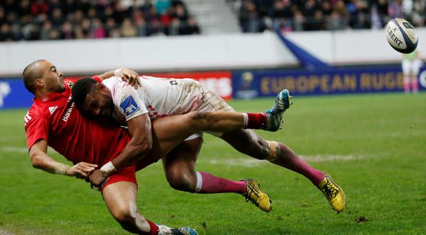 Down and out: Munster star Simon Zebo feels the force of Stade Francais' Waisea Nayacalevu in France