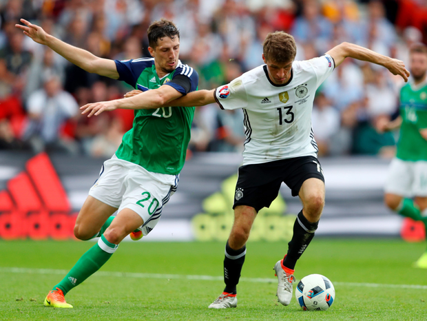 Close attention: Craig Cathcart and Thomas Muller of Germany compete for the ball during their Group C clash in Paris