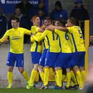 Point made: Paul McElroy is mobbed after hitting Dungannon's late leveller at Mourneview Park