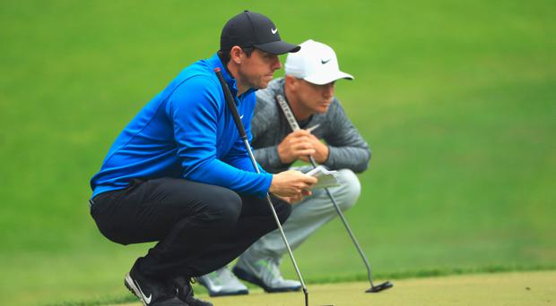 Dialled in: Rory McIlroy (left) and defending champion Alex Noren line up a putt in yesterday's opening round of the BMW PGA Championship at Wentworth
