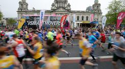 Keep on running: Competitors pass the City Hall in last year's Belfast Marathon