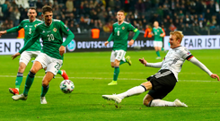 Six appeal: Julian Brandt of Germany scores his team's sixth goal as Craig Cathcart tries to make a block