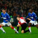 Tough battle: Rangers' Borna Barisic and Glen Kamara battle with Feyenoord scorer Jens Toornstra