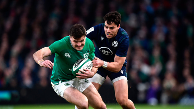 Hands on: Jacob Stockdale is pulled back by Scotland ace Sean Maitland