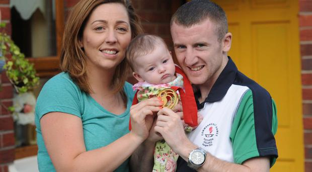 Pride and joy: Paddy Barnes and partner Mari with their daughter Eireann after the boxer came home to Belfast with his Commonwealth Games gold medal last year