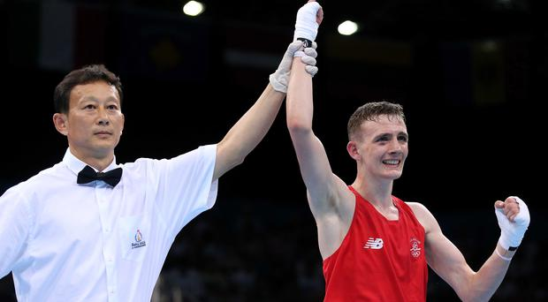 Marching on: Ireland's Brendan Irvine has his hand raised after overcoming Ukraine's Dmytro Zamotayev to earn a unanimous points win in his light-flyweight semi-final. The Belfast boxer is now guaranteed at least a silver medal INPHO