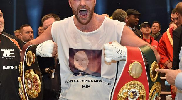 Britain's new world champion Tyson Fury celebrates with the WBA, IBF, WBO and IBO belts after winning the world heavyweight title fight against Ukraine's Wladimir Klitschko in the Esprit Arena in Duesseldorf, western Germany, Sunday, Nov. 29, 2015. (AP Photo/Martin Meissner)