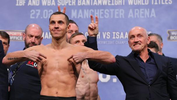 Promoter Barry McGuigan, right, and Carl Frampton gesture behind the head of Scott Quigg during the weigh-in