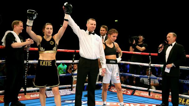 Katie Taylor has her hand raised in victory