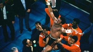 Leon Spinks celebrates as his entourage holds him aloft after his 15-round split decision victory over world heavyweight boxing champion Muhammad Ali in Las Vegas in 1978 (AP)
