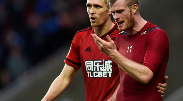 Hard to take: Chris Brunt (with Darren Fletcher, left) is in disbelief after getting hit by a coin thrown by one of his own WBA fans