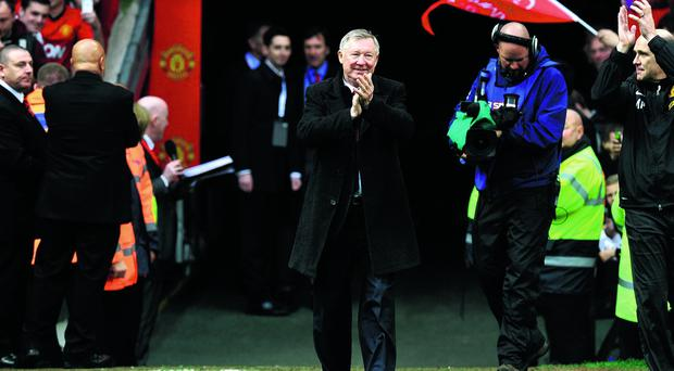 Sir Alex Ferguson walks onto the pitch to lift the Barclays Premier League trophy after the Barclays Premier League match at Old Trafford, Manchester.
