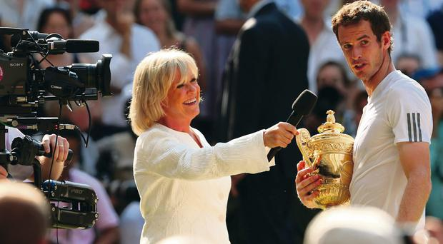 Andy Murray of Great Britain speaks with Sue Barker as he holds the Gentlemen's Singles Trophy