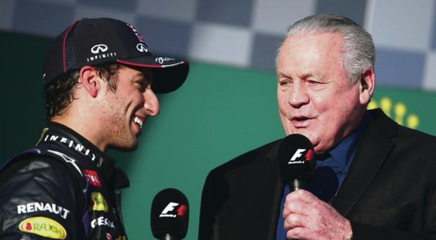 Daniel Ricciardo of Australia and Infiniti Red Bull Racing is interviewed on the podium by Alan Jones