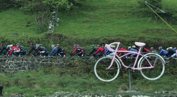 Here we Giro: Cyclists fail to notice a strangely dressed angler as they squelched along the coast road on Saturday