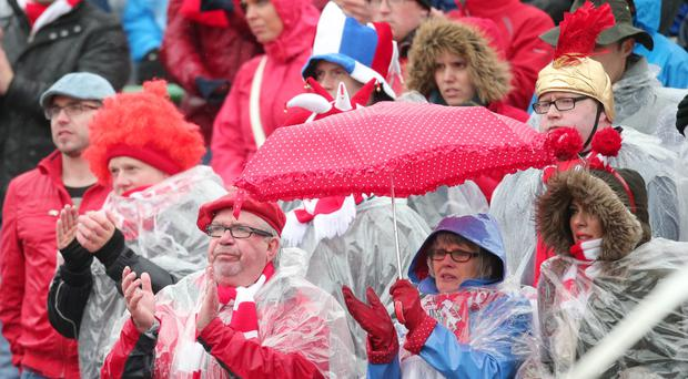 Oval and out: Portadown fans brave the weather by sheltering under a turnip, sorry, umbrella.